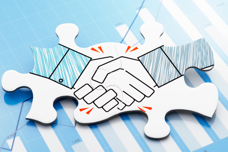 Handshake jigsaw puzzle pieces on blue chart. Concept image of business partnership and agreement.