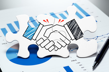 Handshake jigsaw puzzle pieces on report. Concept image of business partnership and agreement.
