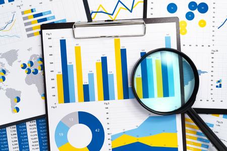 Análisis de informes de marketing. Recopilación de datos estadísticos. Pila de informes. Muchos gráficos y lupa. Foto de archivo