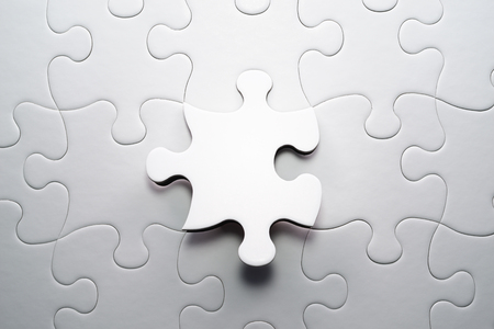 The correct solution. Solving and completing the task. Last piece of jigsaw puzzle. Assembling white jigsaw puzzle pieces.