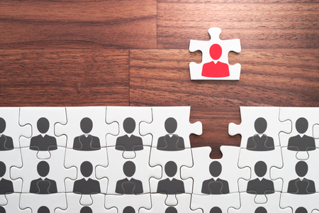 Visionary leader, think positive, different and unique concept. Establishing leadership position. Jigsaw puzzle piece with red businessperson standing out from the crowd.