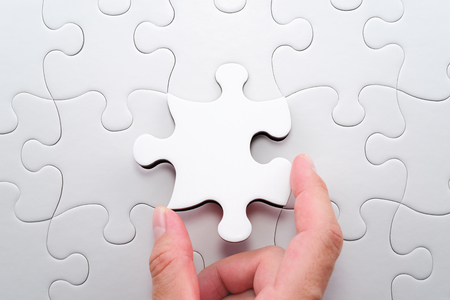 Solving and completing the task. The correct solution. Putting last jigsaw puzzle piece. Assembling white jigsaw puzzle pieces.