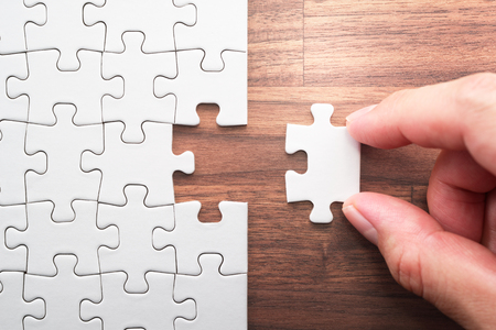 Putting last jigsaw puzzle piece. Solving and completing the task. The correct solution. Assembling white jigsaw puzzle pieces. Stock Photo