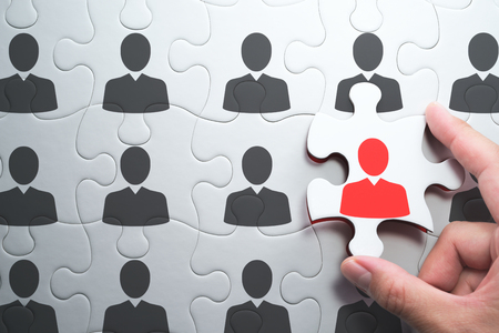 Selecting right people for organization's success. Human resource management and selecting leader concept. Putting last jigsaw puzzle piece with red businessperson. Stock Photo