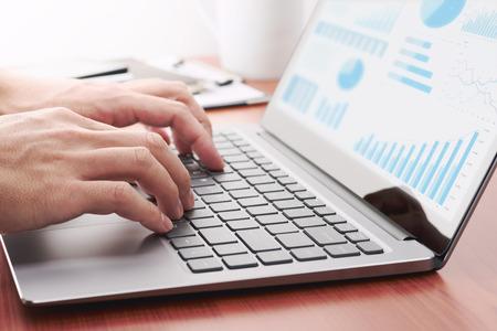 Concepto de análisis empresarial. Empresario preparando informes. Laptop y muchos gráficos. Foto de archivo