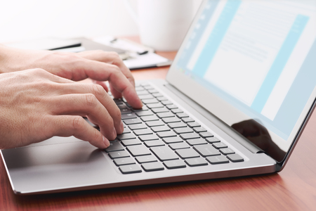 Businessman sending email by laptop. Close up of hand using computer at table. Stock Photo