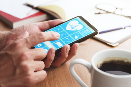 Online healthcare app on smartphone screen.  Closeup of male hands touching smartphone screen at table. Reklamní fotografie