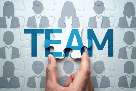 Business team concept. Selecting people and building team.  Connecting last jigsaw puzzle piece.