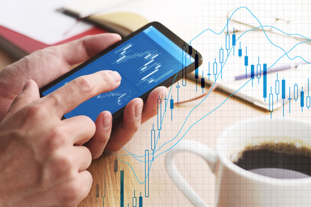 Stock market charts on smartphone screen. Closeup of male hands holding smartphone. Checking financial market. Stockfoto