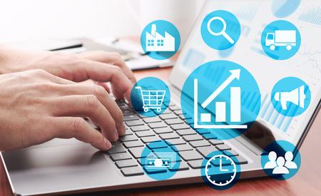 Enterprise-Resource-Planning-Konzept. Geschäftsmann, der Daten analysiert. Viele Grafiken und Diagramme auf dem Laptop-Display. Symbole für die Unternehmensführung.