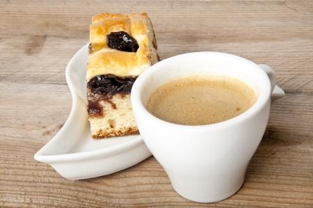 rebanada de pastel: taza de caf� y un trozo de pastel con mermelada de cerezas