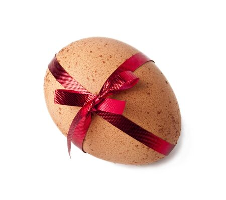 Egg and a red ribbon on white background photo