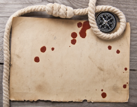 old compass, rope and an old paper on wooden background photo