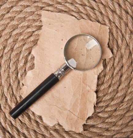 magnifying glass and old paper on the background of the old rope photo