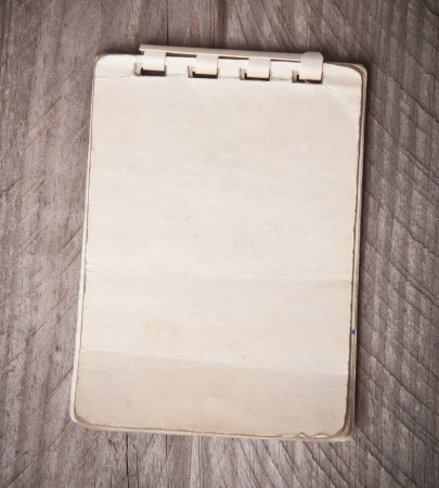 Old notebook on a wooden background photo