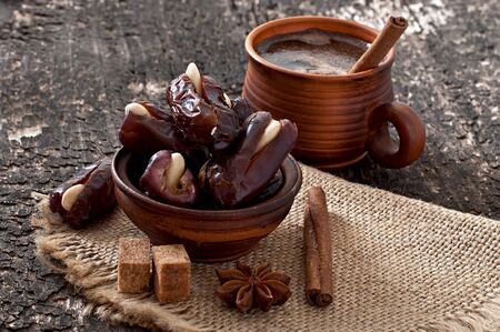 aromatic coffee and eastern dates on old wooden background photo