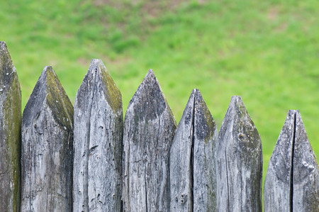 outpost: Fence stakes, a fence made of logs, tapered wooden stakes.
