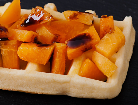 Belgian waffles with pieces of apricot and chocolate sauce. Stock Photo