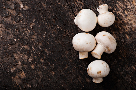 Mushrooms champignons on an old wooden background. Stock Photo