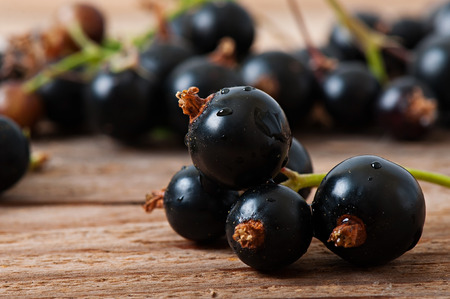 Black currant berries on an old wooden background.