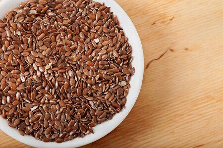 Flax seeds on a white plate, on an old wooden background, top view.
