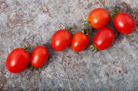 Cherry tomatoes on an old metal background, top view. Stock Photo