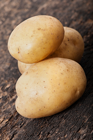 Potatoes on an old wooden background, diet food.