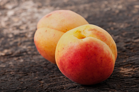 Fruits of apricots on an old wooden background, diet food. Stock Photo