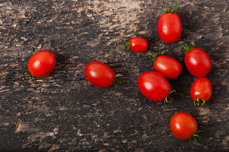 Cherry tomatoes on an old wooden background, top view. Stock Photo