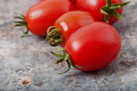 Cherry tomatoes on an old metal background. Stock Photo