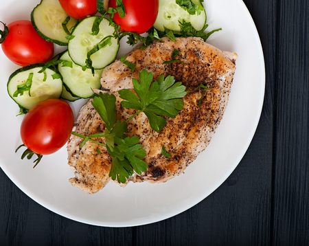 Fried chicken fillet decorated with cherry tomatoes and cucumber, top view.