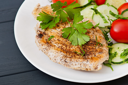 Fried chicken fillet decorated with cherry tomatoes and cucumber.