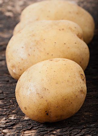 Potatoes on an old wooden background, vegetables. Stock Photo
