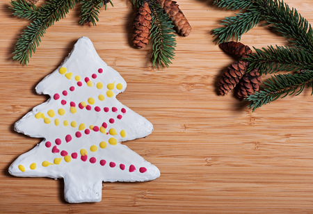 Composition of New Years biscuits and fir branches on a wooden background, Christmas background. Christmas cookies.