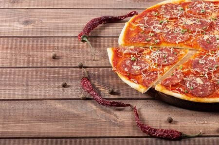 Pizza with salami and cheese on the old wooden background.