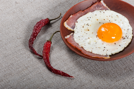 Fried egg on a clay plate, breakfast food.