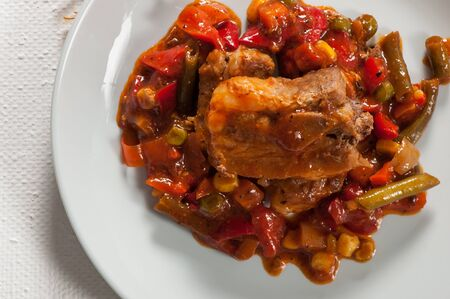 Pork ribs with corn, pepper, tomatoes and green beans. Archivio Fotografico