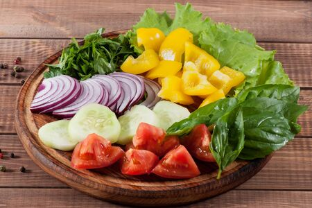 Salad of greens, tomatoes, cucumbers, sweet pepper onions on a wooden background.