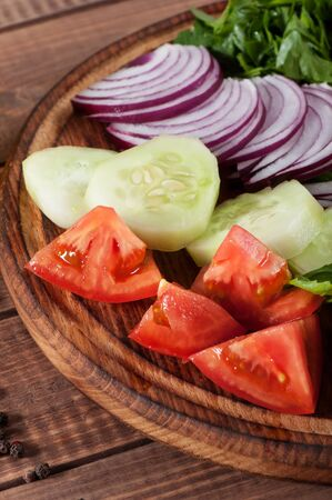 Salad of greens, tomatoes, cucumbers, onions on a wooden background.