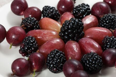 Fresh sweet fruits grapes, blackberries and gooseberries on a light plate. Archivio Fotografico