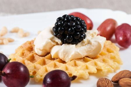 Sweet waffles with sour cream and fruit on a light background.