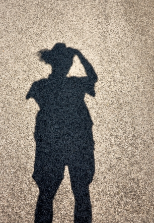 shadow of standing man with straw hat