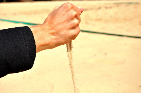 closed fist: Leaking sand from closed fist Stock Photo