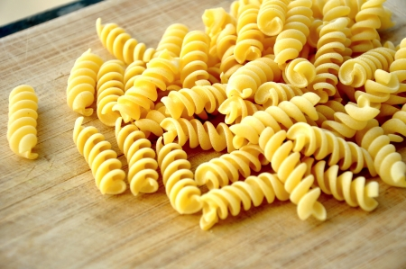 uncooked great italian fusilli on wooden cutting board