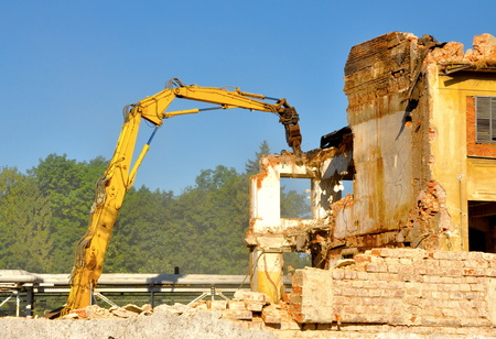 Demolition of industrial building by excavator photo