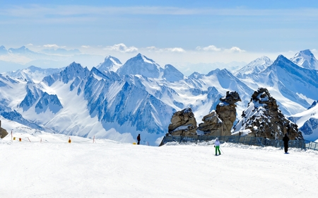 beautiful winter panorama of alps with skiers