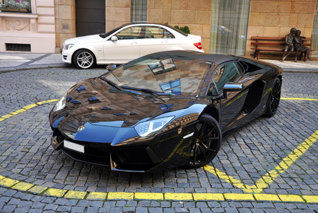 black new lamborghini aventador near luxury hotel