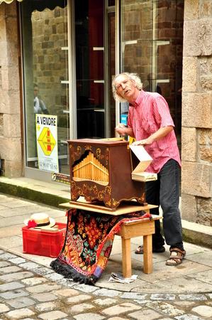 BRETAGNE, FRANCE., JULY 29, 2009: man playing on barrel organ in France