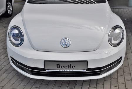 dream car: PRAGA, LA REPÚBLICA CHECA, 02082015 - A estrenar blanco aparcamiento Volkswagen Beetle en Praga con otros coches de VW en frente de tienda de coche Volkswagen