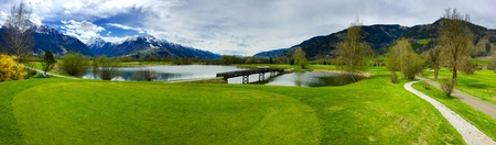 Beautiful golf resort with wooden bridge across the lake in Zell am See in Alps with big mountains behind Stock Photo